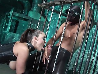 Mistress in latex corset is fucked by two submissive guys from the cage